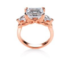 This rose gold masterpiece comes from MaeVona and features an Emerald cut diamond in the center and pear shaped diamonds on the sides. #wedding #ring