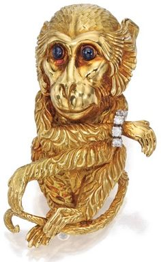 18 Karat Gold, Platinum, Sapphire and Diamond Brooch, David Webb The textured gold monkey set with two round cabochon sapphire eyes, the wrist set with round diamonds weighing approximately .20 carat, gross weight approximately 31 dwts, signed Webb.