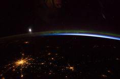 A thin green line of the aurora borealis (northern lights) crosses the top of this photograph, taken by an astronaut on the International Space Station. The moon appears as a white disc just above the aurora. Airglow appears as a blue-white cusp along the Earth's limb. Russia's capital city, Moscow, makes a splash of yellow light and is easily recognized by the radial pattern of its highways.