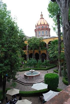 Courtyard of the Centro Cultural Ignacio Ramirez with dome of the Purisima Concepcion Church in the background. In San Miguel Allende, Guanajuato, Mexico