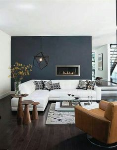 Living room inspiration with dark wood floors, navy accent wall and tan leather elements