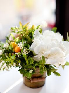 Cherry tomatoes on the vine, baby artichokes, oregano and mint with blooming peonies