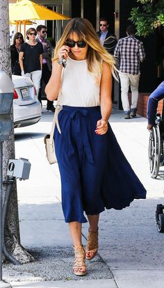 Lauren Conrad wears a white tank top tucked into a blue midi skirt with nude leather platform sandals, a white shoulder bag, and tortoiseshell sunglasses