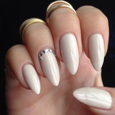 Cream coloured nail polish with some embellishments. Clean finish.