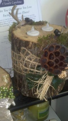Candle holder made from a tree. With woodsy lookin decor. Ribbon looks like burlap