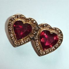 A wonderful Victorian Revival costume pin c1930s.The glowing red glass hearts are set in bezels and framed with a heavily embossed domed frame.The