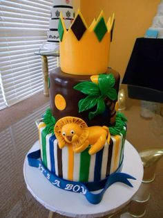 King of the Jungle Baby Shower Cake - * Two tier strawberry cake. The top tier is modeling chocolate with fondant decorations. The bottom tier is butter cream with fondant stripes. The lion is also fondant. Beautiful Cakes, Amazing Cakes, Jungle Cake, Jungle Theme, New Orleans King Cake, Fondant Decorations, Jungle Decorations, Lion Cakes, King Cake Baby