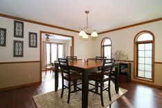 Craftsman Dining Room with Arched window, Chair rail, Crown molding, Hardwood floors, Pendant light