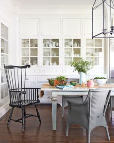 This California farmhouse kitchen built-ins hold all her ironstone and glassware. The Windsor chair is by Ethan Allen; the wicker seats are Janus et Cie. White Dove by Benjamin Moore covers the walls.   - CountryLiving.com