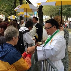 Clergy serve Communion on the Benjamin Franklin Parkway during the papal Mass. #PVatPope