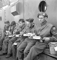 Soldiers of the 9th Canadian Infantry Brigade eating aboard a landing craft en route to France, 6 June 1944. Photographer: Ken Bell