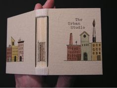"""Unique book: Urban Studio, 2008. Collaboration between James Reid-Cunningham and book artist Laura Davidson, who created the watercolor images of the Boston skyline, and who decorated the cover in watercolor, typewritten text, and ink. Open joint binding covered in Nideggan paper. Sewn using a packed long stitch and linen thread. 2 3/4"""" x 2 1/3"""" x 3/4"""". 7 x 5.2 x 2 cm."""