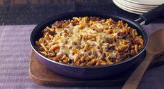 Υλικά για 2-4 άτομα ζωμός λαχανικών 350 γρ. κοφτό μακαρονάκι, μέτριο Για τον κιμά 1/2 φλιτζ. ελαιόλαδο 1 μεγάλο ξερό κρεμμύδι, ψιλοκομμένο 1 σκελίδα σκόρδου, λιωμένη 1 κουτ. γλυκού πελτές ντομάτας 400 γρ. κιμάς μοσχαρίσιος, κατά προτίμηση από σπάλα 2 μεγάλες, ώριμες ντομάτες, τριμμένες στον τρίφτη αλάτι, πιπέρι 1 κοφτό κουτ. γλυκού καστανή ζάχαρη 1/2 φλιτζ. ψιλοκομμένα φύλλα μαϊντανού 1 φλιτζ. χονδροτριμμένο κασέρι 1/2 φλιτζ.χονδροτριμμένη γραβιέρα Εκτέλεση