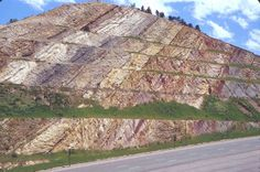 TILTED ROCK LAYERS:  The sedimentary layers in this large roadcut near Denver, CO. can be clearly recognized by the variation in color. This deformation is related to the uplift of the Rocky Mountains