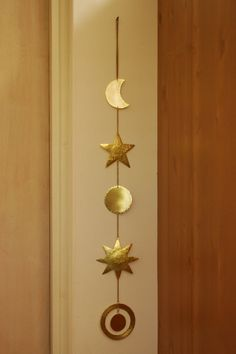 This unique celestial brass decor includes a moon, a star, a full moon, a sun and a planet with ring. The brass is shiny and vibrant and works with