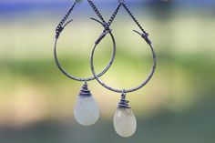 Natural green sapphires hang on elegantly curved mini crescent horns. Hand stamped and wire-wrapped in sterling silver. Topped off with clear faceted quartz crystals. All sterling silver with the exception of the brass chain. Total length from top of earwire: 3″