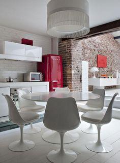 Une cuisine blanche ouverte sur un salon au même code couleur où le rouge du frigidaire et celui de la toile accrochée sur le mur en pierres du salon sert de fil conducteur. Design, sobre, lumineux, superbe réalisation !