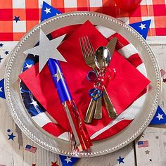 Create fireworks at your 4th of July table by layering place-settings with star cutouts and silver metallic chargers.