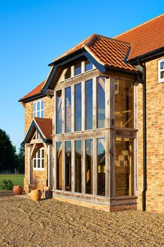"""The oak is treated with Sadolin Volcanic Ash oil which gives a warm grey patina and matches the large oak-framed window at the front. Oak Framed Extensions, House Extensions, Stuart House, Oak Framed Buildings, Oak Frame House, Volcanic Ash, Barn House Plans, Timber House, Dream House Exterior"