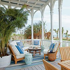 Palm trees swaying in the breeze bringing with it the salty scent of the ocean. This is an ideal Coastal Living Ultimate Beach House porch!