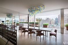 Midcentury-modern–style chairs join a custom-made rosewood-top table in the dining area, which offers views of the Upper East Side.