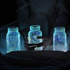 Mason jars with glow in the dark paint splattered in them. Sit in light all day to charge and glow all night!
