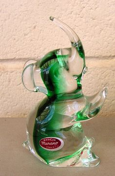 Beautiful green and clear glass elephant measures 6 1/4 inches tall and 3 3/4 inches from front to back. Its about 2 inches wide.    Its in