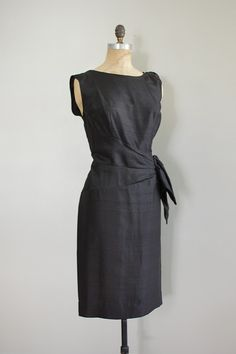 Vintage 1960s black raw silk cocktail dress, sleeveless with gathered silk applique at one shoulder and asymmetrical draped and swag waist.