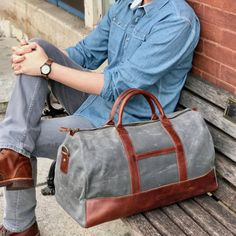 vintage brown leather waxed canvas weekender duffel brick background
