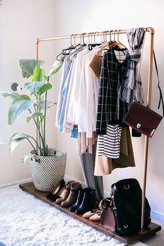 This rack has a modest number of items, leaving room for a plant! With the exception of the purse and scarf hanging off the end of the rack, this garment rack is attractively done.