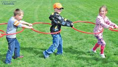Kindergartners, from left, Hunter Schurger, Lane Geisner and Skye Schultz run around in hula hoops at one of the stations during Field Day on Thursday, May 23. Students pretended they were a snake and took turns playing the head and tail of the snake. The purpose of the game was for the head to catch the tail.