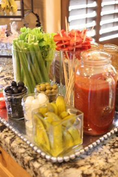 Olives, Onion, Celery, Limes and lemons, cornichons, string cheese, hot sauce, toothpicks, peppercini, cooked but cold cut andouille sausage, Bloody Mary mixture, vodka