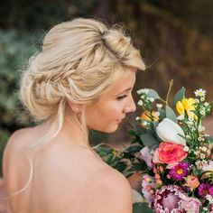 """For today's bohemian bride, a messy updo with loose braids is effortlessly beautiful. One tip is to leave two wavy strands on both sides of your hair for…"""