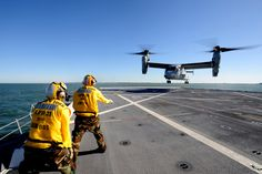 Aviation Boatswains Mate Handler 2nd class Dustin Shipman assigned to the amphibious transport dock ship, USS  New York (LPD 21), directs an MV-22 Osprey to land on the flight deck. This flight marks the first aircraft to land on the flight deck. #americasnavy #usnavy