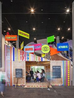 Erected on site in just two weeks and entirely hand-crafted, the timber single-storey structure is topped with neon signs emblazoned with words that originated from workshops held with youth arts group Birmingham 2022.