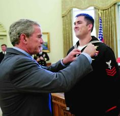 Marcus Luttrell receiving a well deserved badge from Dubya. TFM.