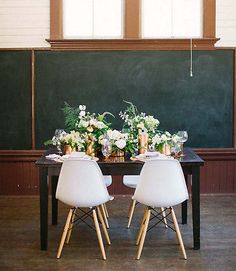 Swoon...these chairs are absolutely perfect for the modern wedding reception. The chalkboard backdrop is a fun addition.