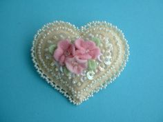 Hi! Like so many of us, I just love hearts, so making this little pin was such a joy! I used a nice piece of off white wool blended felt, for the heart. I added lots of matching lacy beadwork, sequins and dainty pink blossoms for a sweet, romantic look. Each little flower has a Swarovsky crystal center. This heart pin is 2 3\/4 inches across and 2 1\/2 from top to bottom. Its all hand stitched, no glue used! This is a very clean, non smoking home. I ship my items, very sweetly packaged…