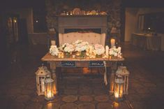tufted loveseat behind large wooden sweetheart table