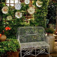 Cottage Garden...love the plates on the trellis!