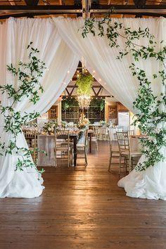 Barn Wedding Reception with a Draped Entrance with Modern Greenery https://heyweddinglady.com/earthy-organic-wedding-style-modern-greenery/ #weddings #wedding #weddingideas #realweddings #southernweddings #weddingreception #reception #greenery #weddingdecor #weddingflowers #barnweddings