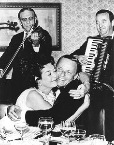 Rosalind Russell gives Frank Sinatra a squeeze at 25th anniversary party he threw for her and husband Frederick Brisson in 1966.