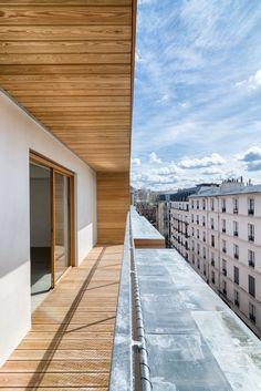 Photographies d'architecture de ce magnifique immeuble de logements sociaux associé à un équipement public. Loggias en bois, façades et coursives blanches.