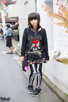 """17-year-old Amamin on the street in Harajuku wearing a Glad News """"Bondage Bear"""" sweater with a Super Lovers skirt, skeleton tights, an Algonquins bag, and Sexpot Revenge accessories."""