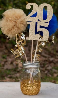Graduation Party Centerpiece. This glittering 'Class of 2015' table centerpiece for graduation decoration will create a stunning visual effect with the gold glittering mason jar. It will shine your bright future through. http://hative.com/diy-graduation-party-decoration-ideas/ #partydecorationideas
