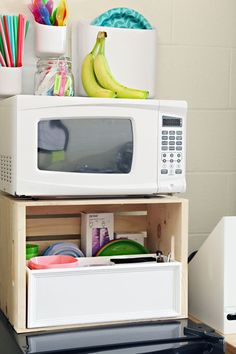 Use a Wood Storage Crate above the refrigerator to store kitchen items, a separate box inside helps corral items and keep it organized.  Above the microwave, attach Urbio Pockets (Container Store) with Command Strips to give more storage.