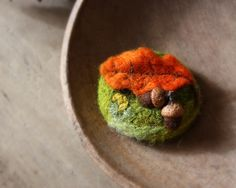 A little wool scene to wear.  I made this brooch by needle-felting wool roving.  The two impossibly tiny wool acorns have a real cap.  A scene from the forest floor.