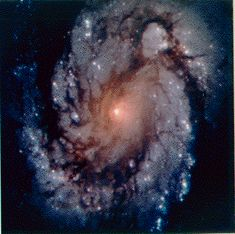 The Spiral M100 is a large galaxy similar to our own Milky Way, containing over 100 billion stars. It is over 150 million light years away, so the light we see left when dinosaurs roamed the Earth. The picture was taken in 1993 with the Wide Field and Planetary Camera 2 on board the Hubble Space Telescope.