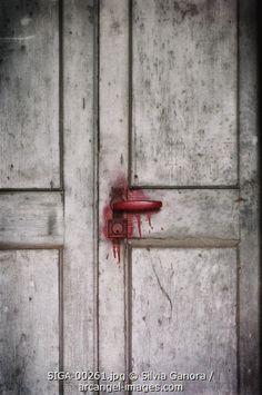 Closeup shot of a bloody doorknob in a rotten door #bookcovers #door #bloody #blood
