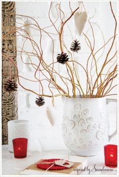 Simple yet fun....curly willow with pine cones as ornaments hanging by candy cane colored string.